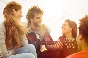 30673439 - happy group of friends enjoying the summer outdoor playing guitar and singing together